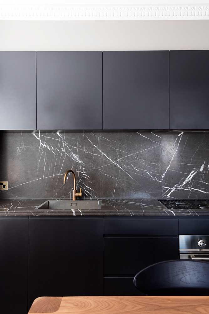 A placa de granito preto na parede completou o visual moderno e elegante da cozinha