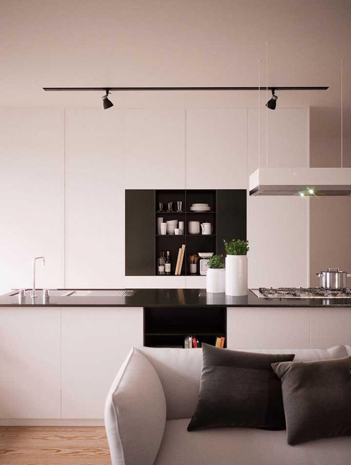 A bancada da cozinha contou com a aplicação de granito preto, combinando com armários planejados