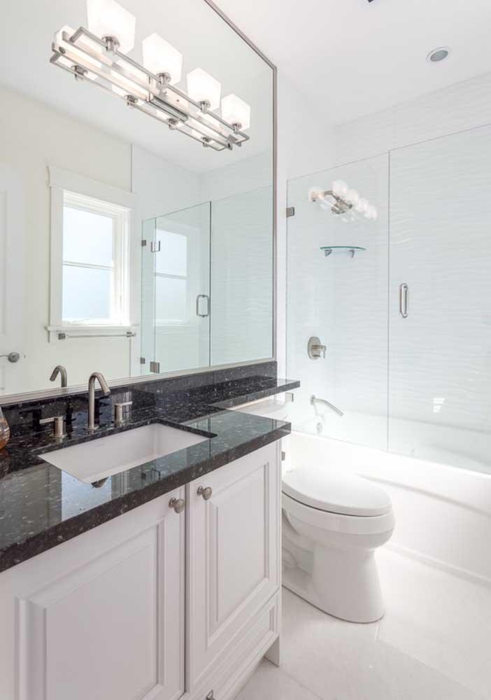 Nesse banheiro, o tampo de granito preto recebeu um recorte diferenciado