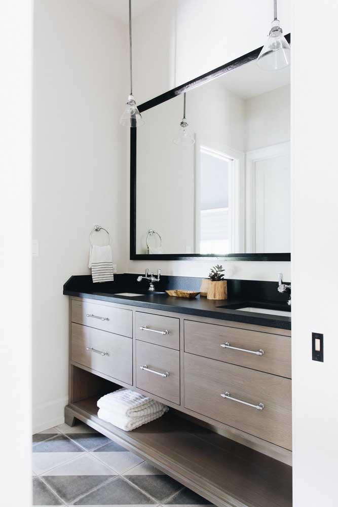 Gabinete simples de banheiro com tampo em granito preto; repare que a moldura se liga diretamente à bancada