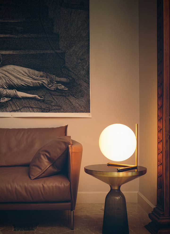 A sala de estar fica muito melhor com a luz difusa dessa luminária circular que parece flutuar sobre a mesinha lateral