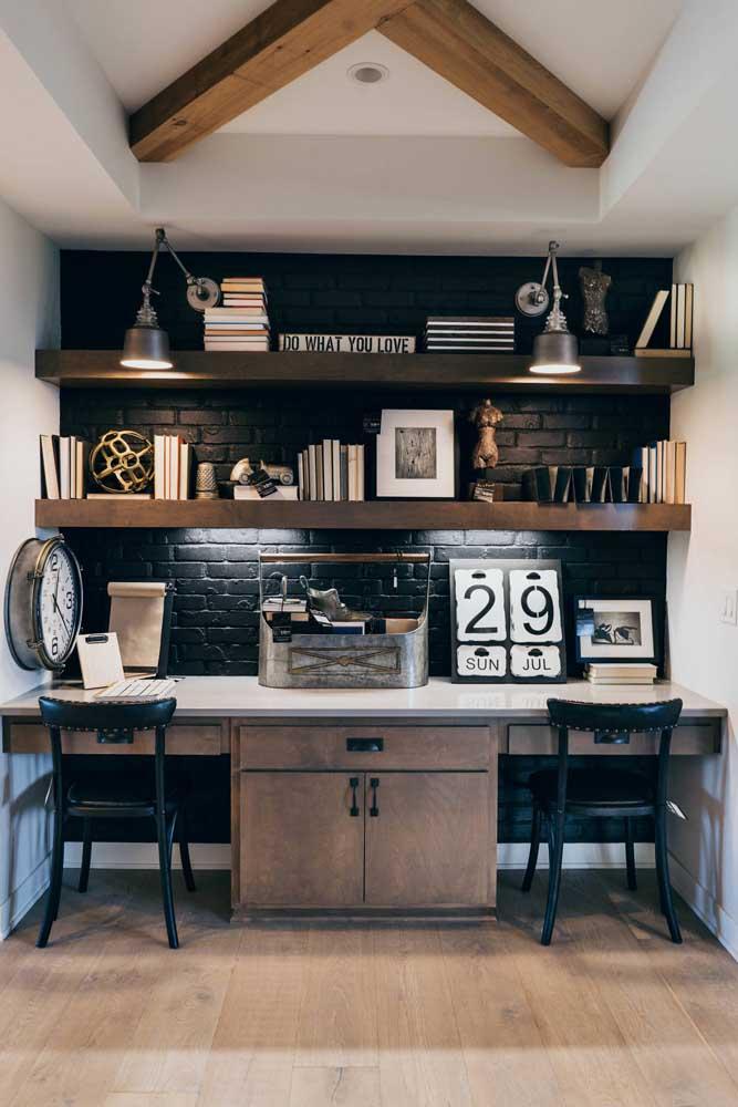 Nesse home office cheio de estilo, a tradicional luminária de mesa foi posicionada na altura da última prateleira; para completar a iluminação, fitas de led sob a prateleira