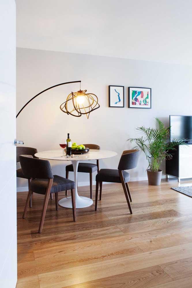 A mesa de jantar ganha um clima intimista e acolhedor com a luminária direcionada