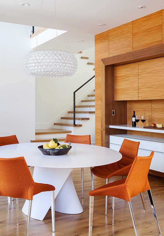 Aqui é a base da mesa de jantar redonda branca que se destaca; a cor das cadeiras forma um lindo contraste com a mesa