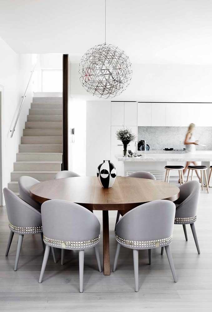 Mesa de jantar redonda com sete cadeiras; destaque para o lustre em formato circular