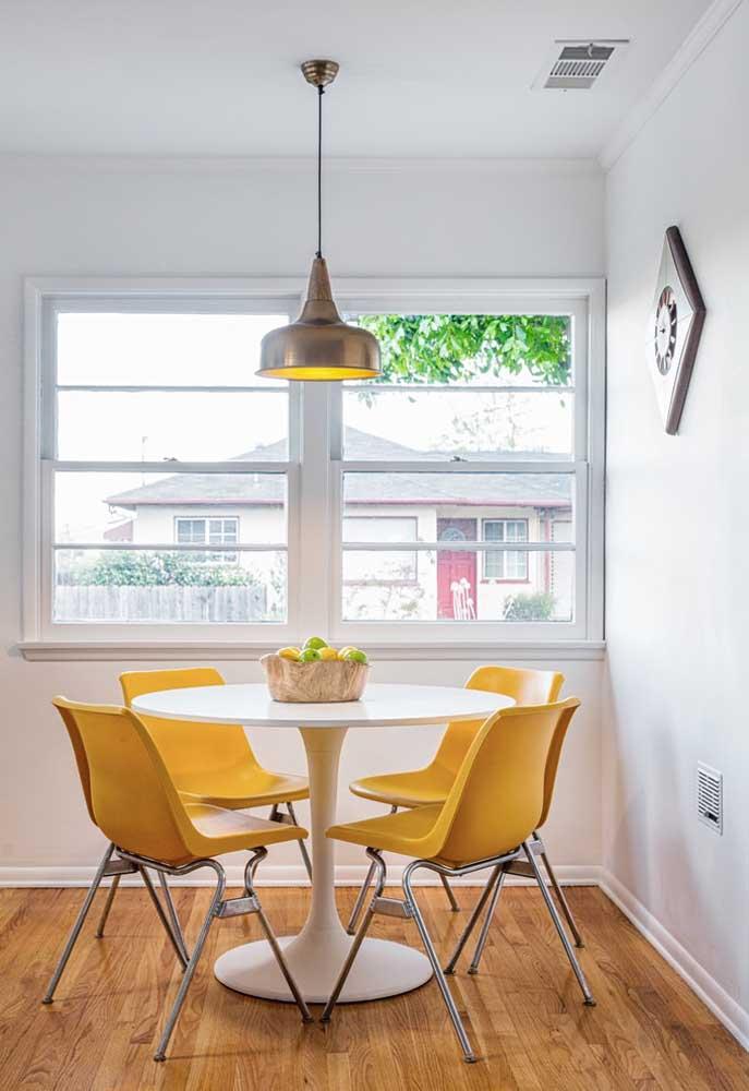 Mesa de jantar redonda simples; o diferencial aqui está na cor das cadeiras