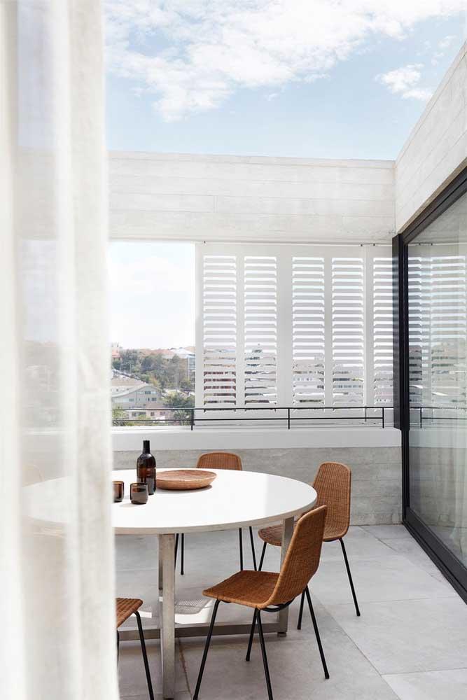 A fibra natural das cadeiras garante um toque de rusticidade a mesa de jantar redonda branca
