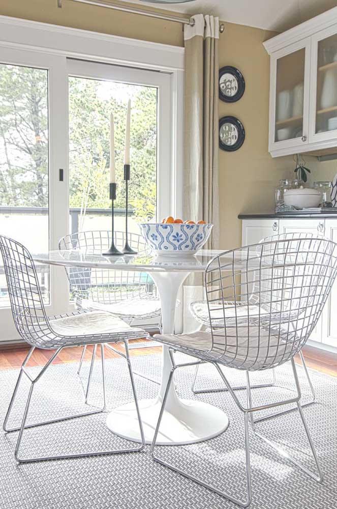 De design clean, essa mesa redonda vem acompanhada de cadeiras aramadas brancas