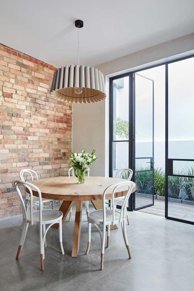 Mesa de jantar redonda de madeira em estilo rústico com cadeiras de design clássico; repare que o lustre segue o mesmo formato da mesa