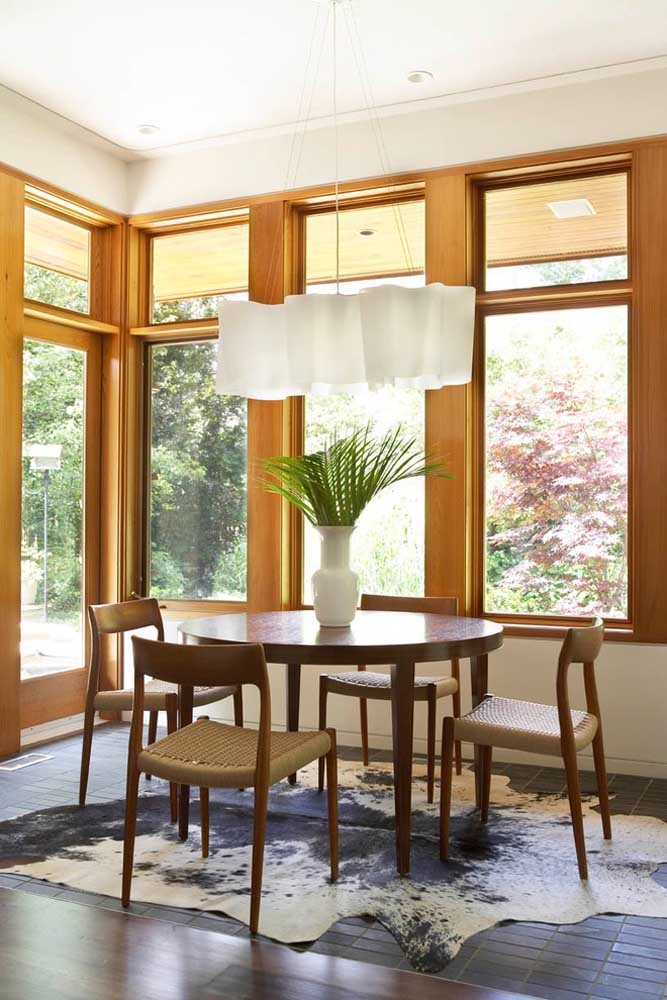 Modelo clássico e tradicional de mesa de jantar redonda; note que o tapete de pele animal não acompanha o formato da mesa