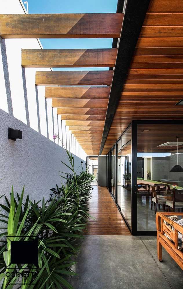 Pergolado de madeira com vigas grossas e espaçadas fixadas na parede; repare que a estrutura cobre todo o corredor externo