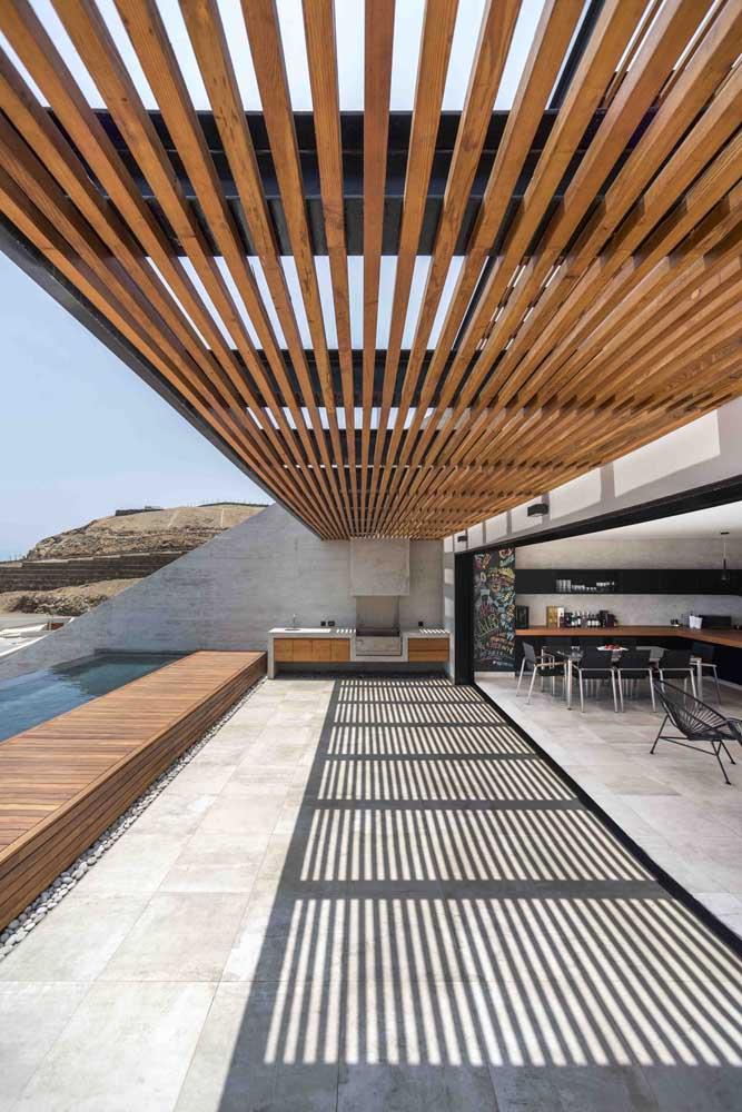 A estrutura metálica preta garante um toque moderno ao tradicional pergolado de madeira