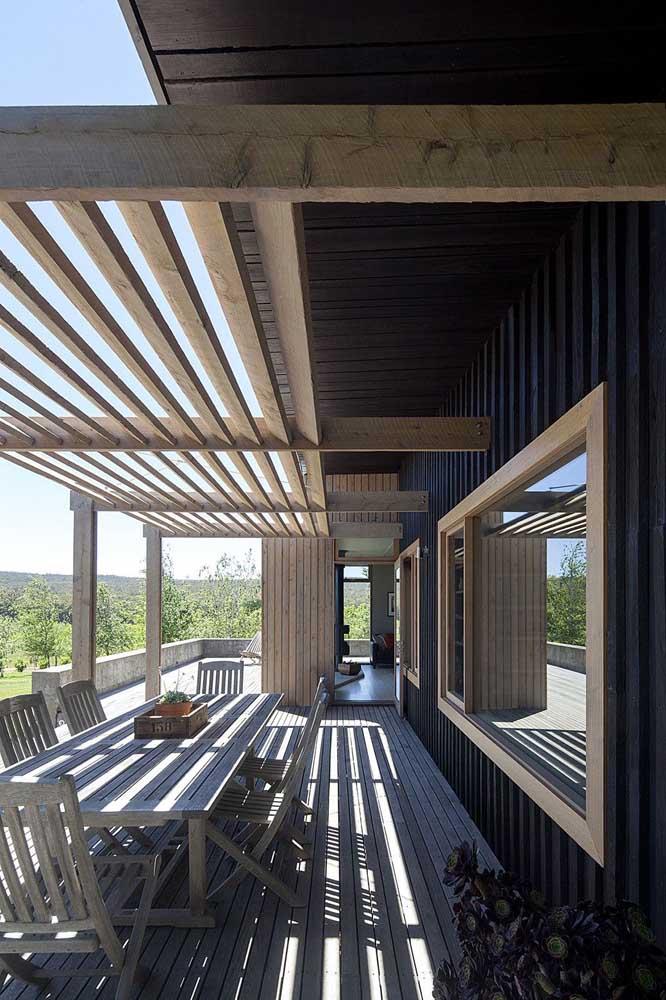 O pergolado de madeira a seguir traz as aberturas vazadas em apenas metade da estrutura, o restante se aproveita da sombra oferecida pelo beiral do telhado