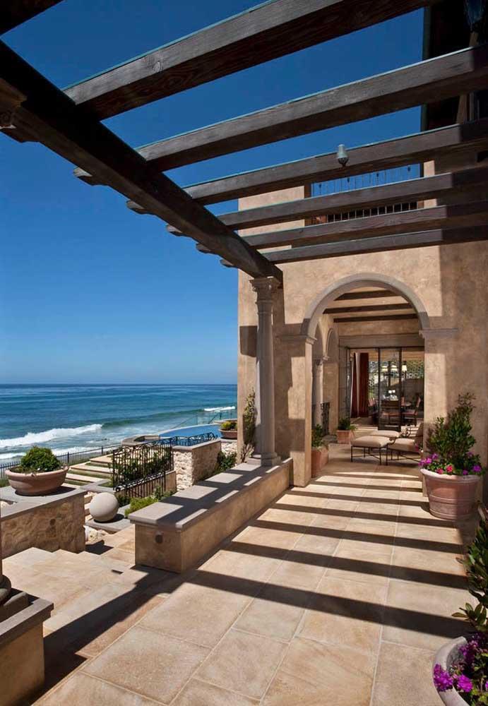 Casa de praia rústica com pergolado de madeira de grandes aberturas