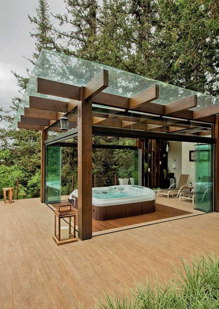 O pergolado de madeira foi o lugar escolhido para abrigar o spa externo; para garantir o máximo de conforto, uma cobertura de vidro