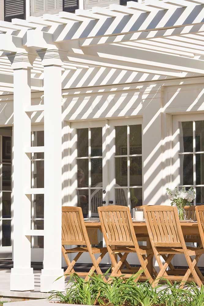 Para combinar com a fachada da casa, a solução foi pintar o pergolado de madeira com tinta branca