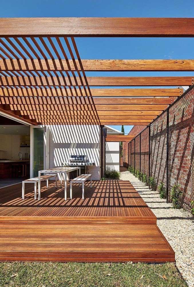 Uma opção é usar o muro da casa como parte estrutural do pergolado de madeira