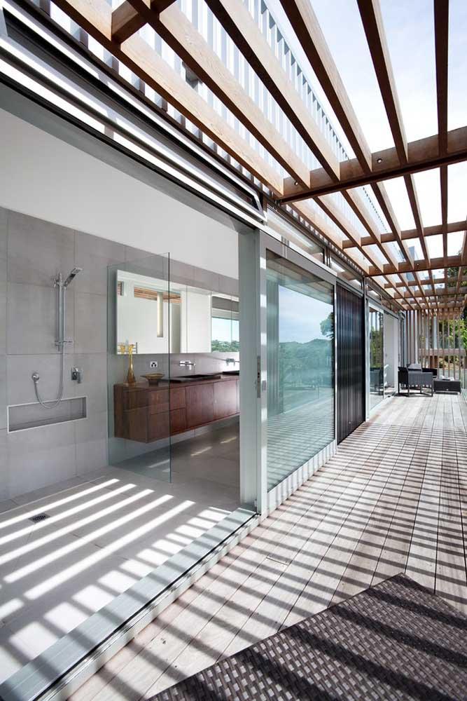 A casa clean apostou em um pergolado de madeira com aberturas maiores