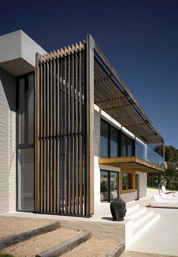 Essa fachada de pé direito alto apostou em um pergolado de madeira grande, capaz de cobrir toda a extensão da casa