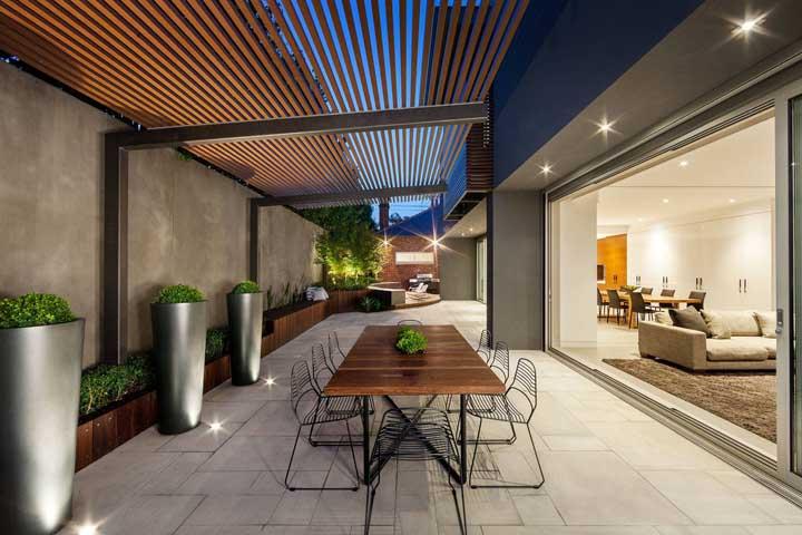 A casa grande e moderna conta com um pergolado de madeira para abrigar com mais conforto os encontros na área externa