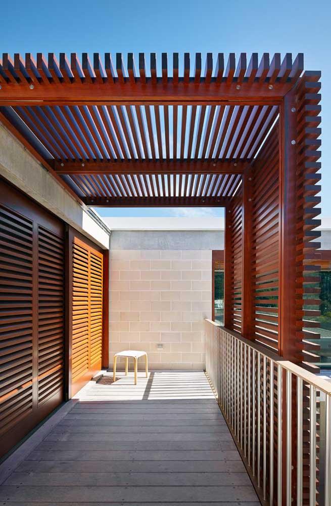 Nessa casa, pergolado e portas dividem o mesmo padrão visual de ordenação das madeiras