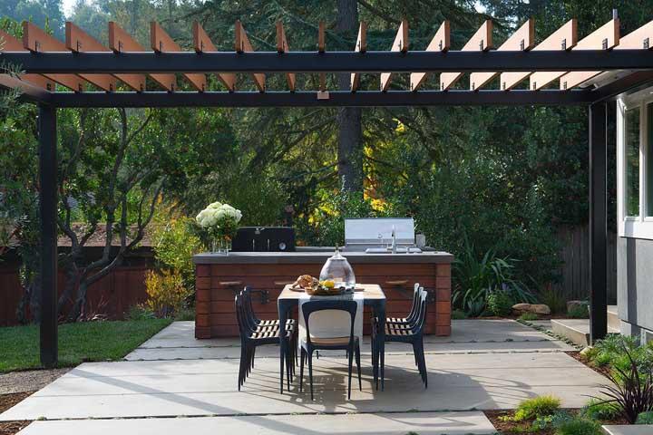 Tudo em harmonia nessa área externa: repare que a cor da madeira do pergolado se repete no balcão gourmet e o preto da estrutura aparece também nos móveis