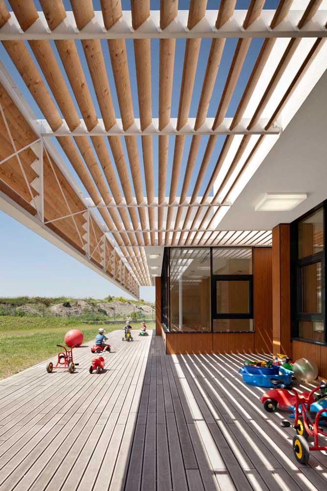 Repare na sombra fresca e agradável que o pergolado de madeira traz para a área externa