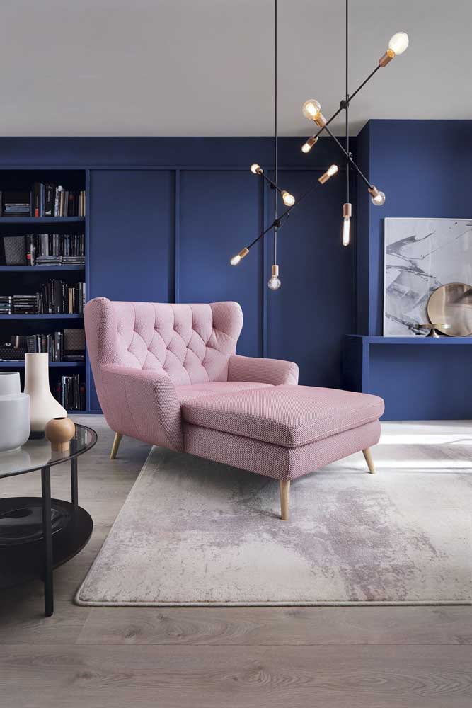 Nessa sala, a poltrona rosa forma um lindo contraste com a parede azul royal