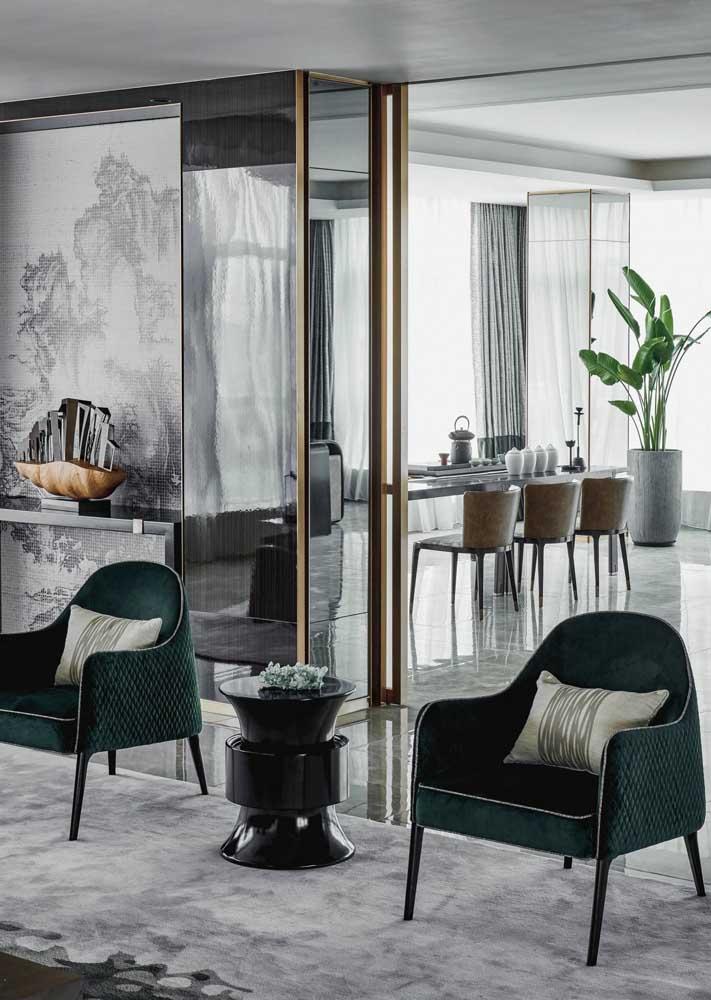As elegantes poltronas verdes dessa sala delimitam a área entre os ambientes integrados