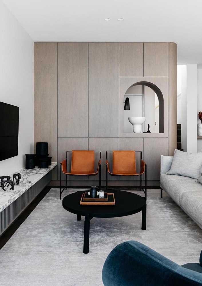 A sala moderna trouxe uma dupla de poltronas de design minimalista; repare que o tom caramelo do couro é o grande destaque da decor