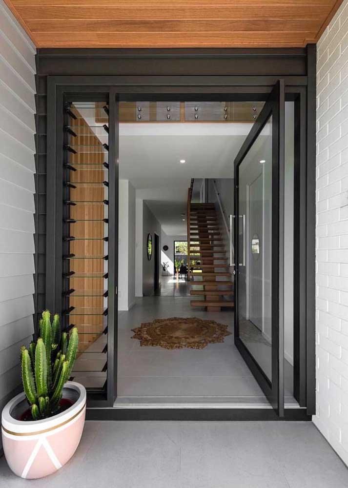 Porta pivotante de vidro com moldura metálica; repare que a lateral da porta permite a passagem de ar