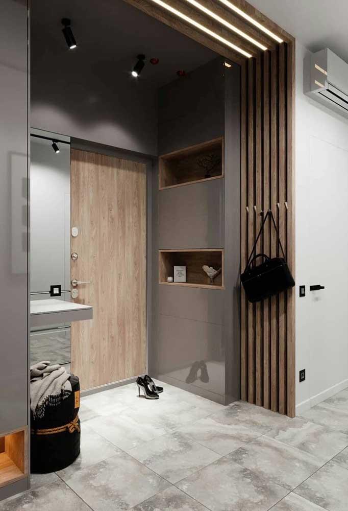 Porta de entrada em tom de madeira natural combinando com os demais elementos do hall