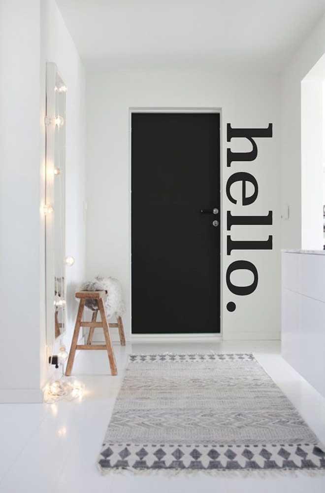 No ambiente todo branco, a porta de entrada preta se torna o grande destaque