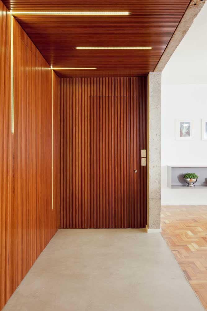 As ripas de madeira que revestem a parede chegam até a porta de entrada promovendo uma linda uniformidade visual
