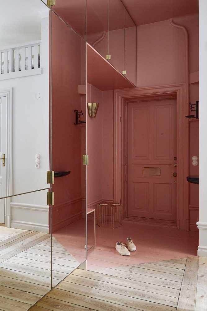 Porta de entrada de madeira em modelo tradicional; repare que a cor da porta acompanha a cor da parede