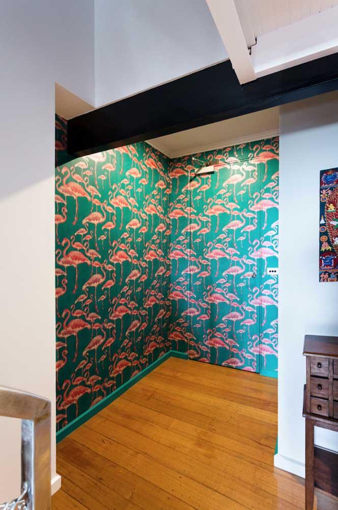 Uma dica muito legal é revestir a porta de entrada com papel ou adesivo; no caso da imagem a seguir, o revestimento de flamingo contorna todo o hall