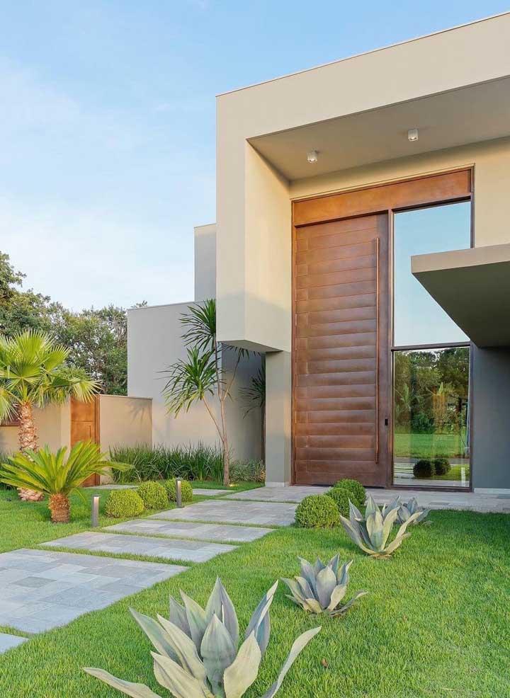 A fachada dessa casa ficou muito mais luxuosa e imponente com a gigante porta de madeira e vidro