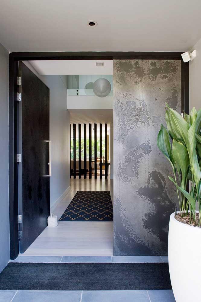 O hall de entrada fica mais elegante com a porta larga na cor preta