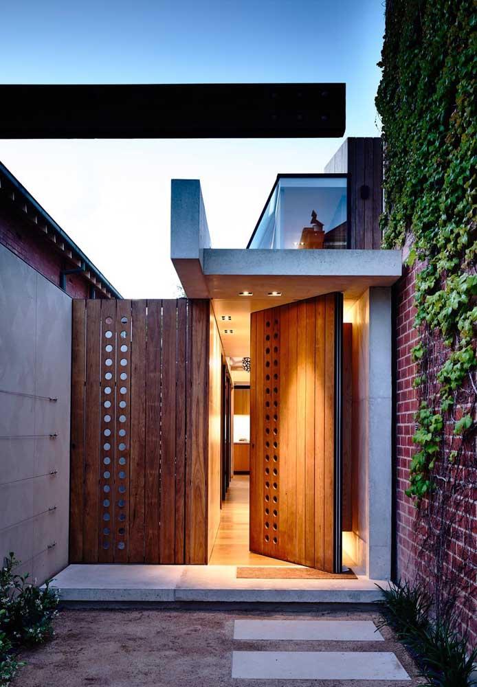 Porta pivotante de entrada de madeira com detalhes vazados