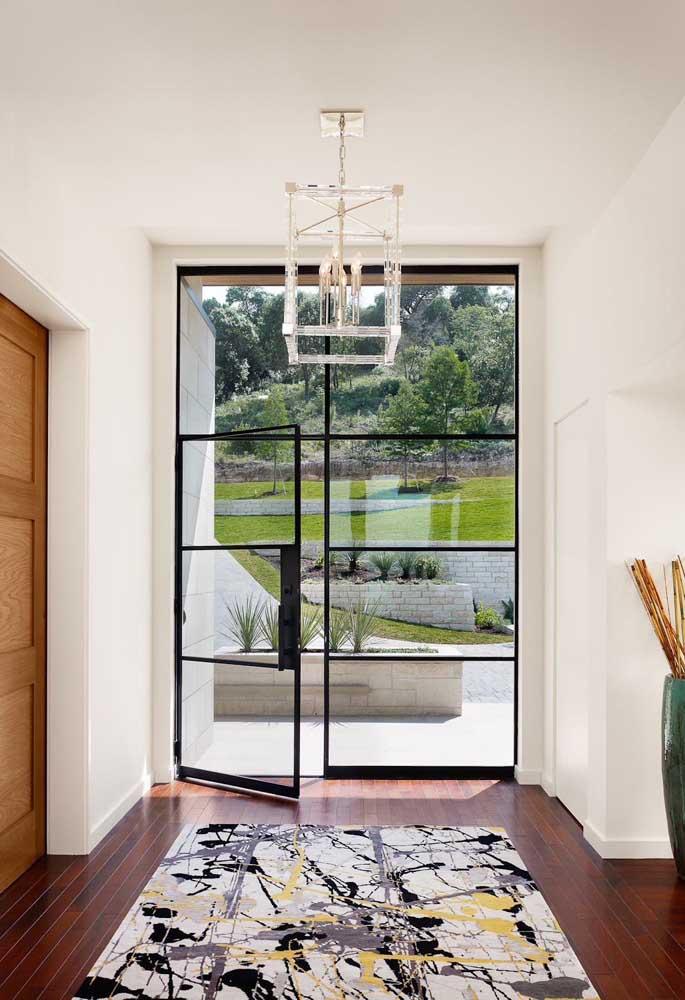 Um lindo modelo de porta de entrada de vidro com moldura metálica; opção moderna e clean para a residência
