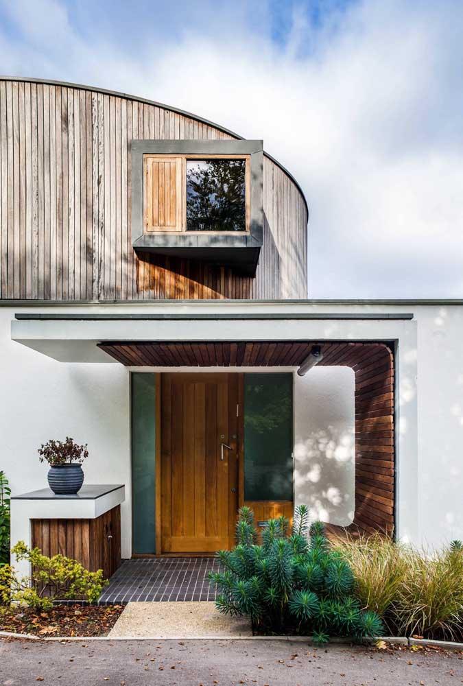 Porta de entrada simples de madeira; o diferencial nesse hall é a estrutura que o cerca