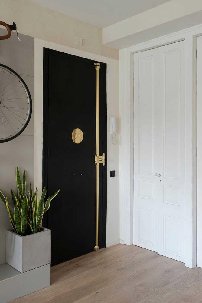 Moderna, essa porta de entrada na cor preta conta com elementos em dourado para criar contraste