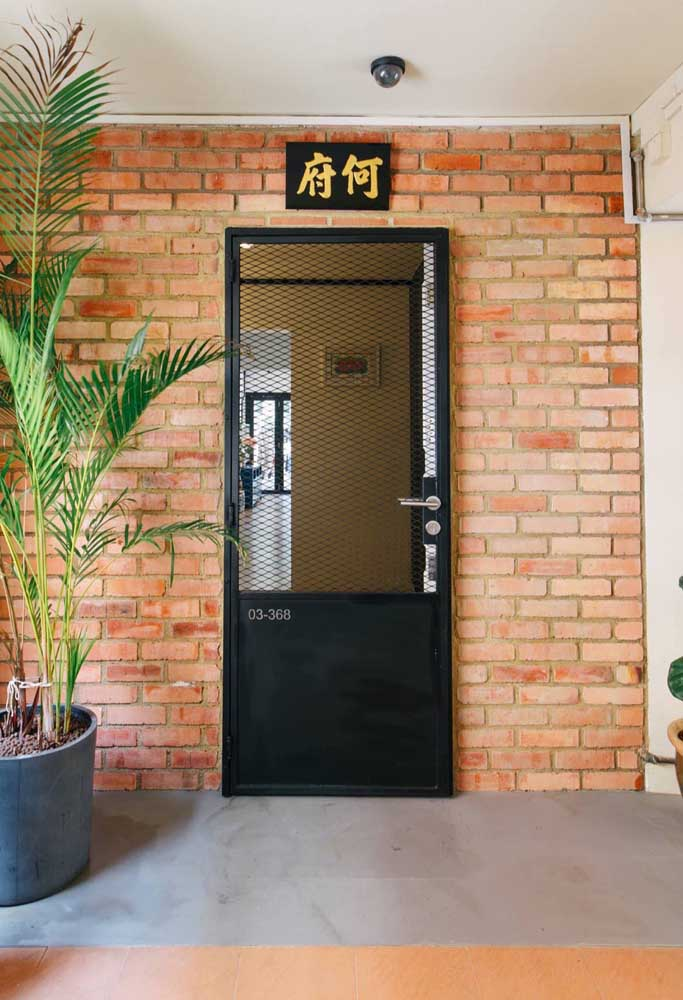 Porta pivotante de vidro para a entrada da casa; para garantir a privacidade foi usado vidro jateado