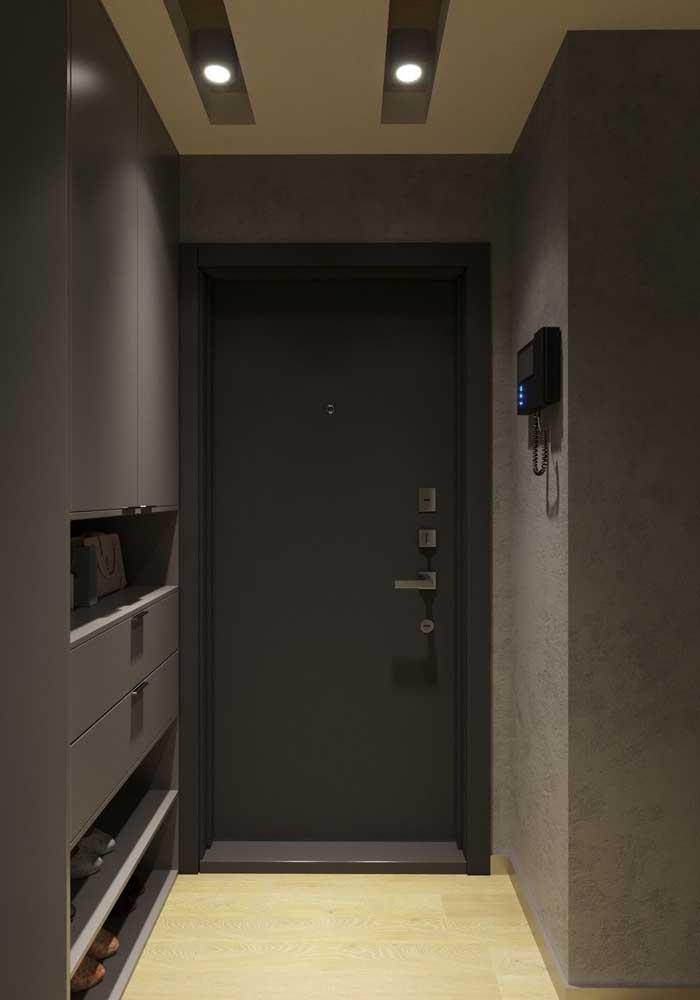O hall de entrada sóbrio e moderno conta com uma porta de madeira pintada de preto