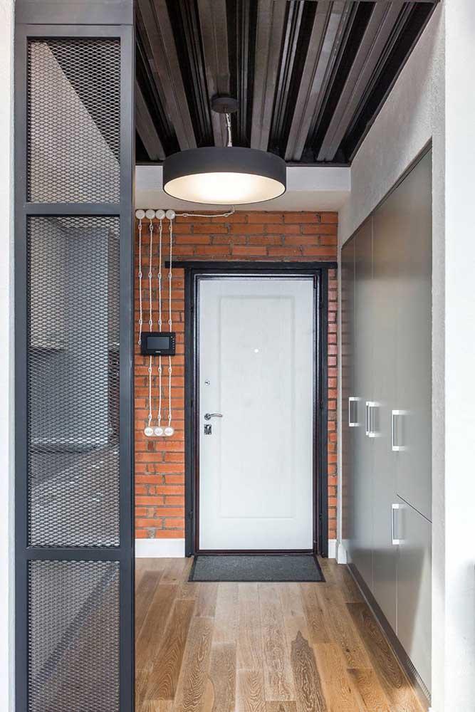 A casa de estilo industrial apostou em um modelo de porta de entrada tradicional pintada de branco e acompanhada por um batente preto