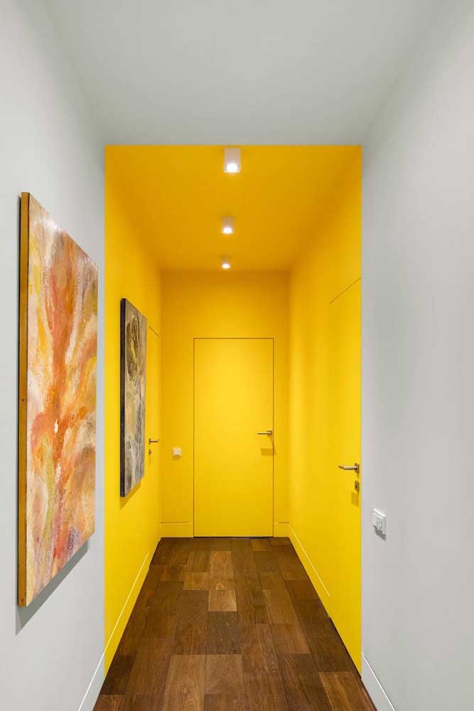 O hall de entrada dessa casa foi demarcado pelo uso da tinta amarela