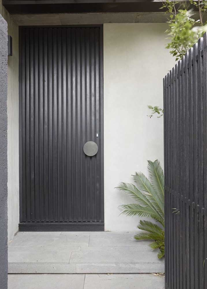 Porta de entrada preta seguindo o mesmo padrão visual do portão