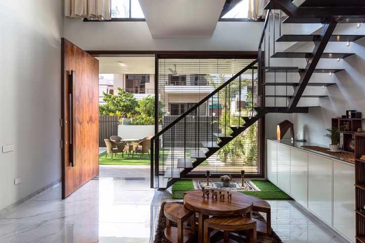 Porta de madeira pivotante para entrada da casa; repare na necessidade de um espaço amplo capaz de contemplar o tamanho da porta