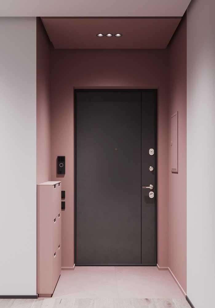 O hall de entrada cor de rosa ficou mais moderno e despojado com a porta de madeira preta