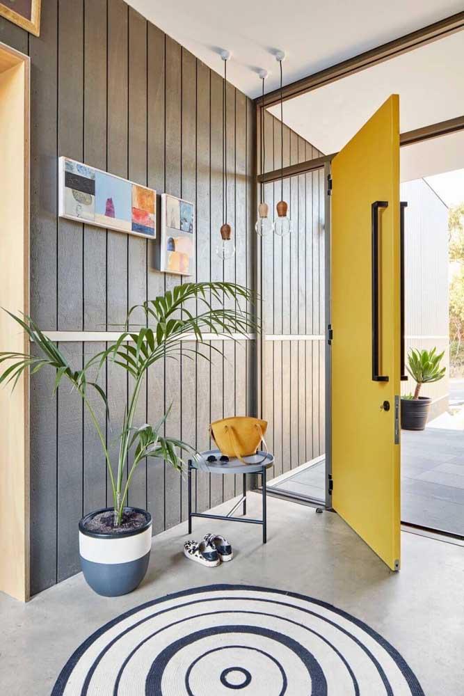 Porta de entrada amarela; repare que a abertura pivotante garante um destaque ainda maior para a peça